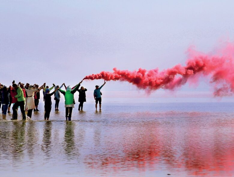 People on a beach with a red smoke flare
